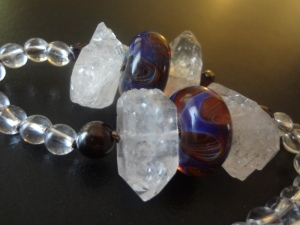 Detail of prayer beads with round quartz, round garnet, artisan-made glass, and rough herkimer diamond beads
