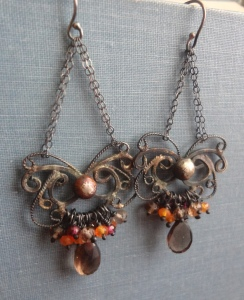 Silver filigree chandelier earrings with patina, smoky quartz, rhodolite garnet, and carnelian beads clustered at the bottom