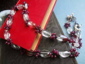 A long ruby and quartz necklace sitting on books