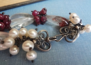 A blackened silver heart hook clasp surrounded by white pearls