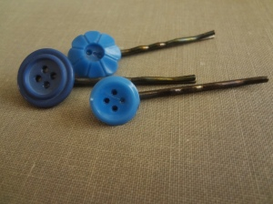 Three bobby pins made with 2 round blue buttons and 1 button that is shaped like a daisy