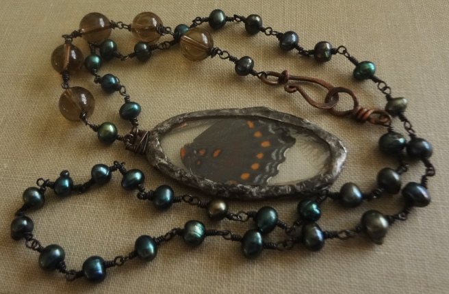 A black butterfly wing with blue and orange spots along its edge encased in a stain glass pendant.  It is attached to a rosary-style chain with peacock blue pearls and 5 larger brown smoky quartz beads.