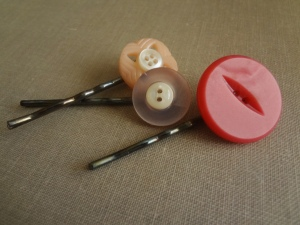 3 bobby pins made to 2 pink bobby pins with smaller white buttons and one larger darker pink button.