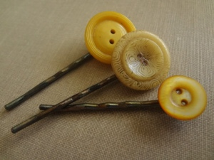 Three bobby pins made with antique yellow buttons on an antique book background